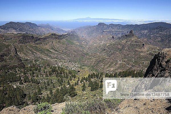 Ausblick vom Roque Nublo  Kultfelsen der Altkanarier  in den Barranco del Chorrillo und die Bergwelt im Westen von Gran Canaria  hinten Teneriffa mit Vulkan Teide  hinten rechts der Kultfelsen Roque Bentayga  Gran Canaria  Kanarische Inseln  Spanien  Europa