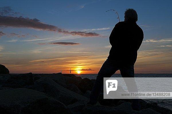 Fisher at sunset on the pier  Lohme  Ruegen island  Mecklenburg-Western Pomerania  Germany  Europe