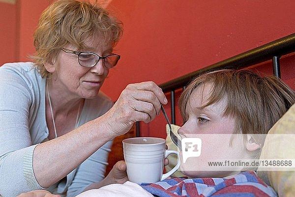 Mutter versorgt kranken Sohn im Bett,  Symbolbild,  Erkältung,  Pflege,  Kindheit,  Eltern,  Deutschland,  Europa