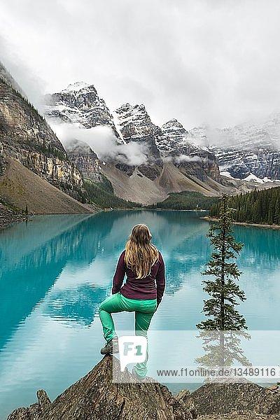 Junge Frau steht vor einem See blickt in Berglandschaft  Wolken hängen zwischen Berggipfeln  Spiegelung in türkisfarbenem See  Moraine Lake  Valley of the Ten Peaks  Rocky Mountains  Banff-Nationalpark  Provinz Alberta  Kanada  Nordamerika