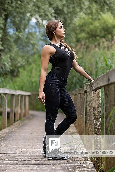 Young woman poses in nature on wooden footbridge