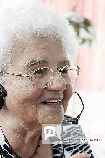 Eine alte Dame telefoniert  hoch erfreut  zum ersten Mal über ein Headset  Sprechgarnitur oder Kopfsprechhörer  Deutschland  Europa