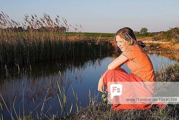 Verträumt kniendes Mädchen an einem kleinen See in abendlicher Sonne