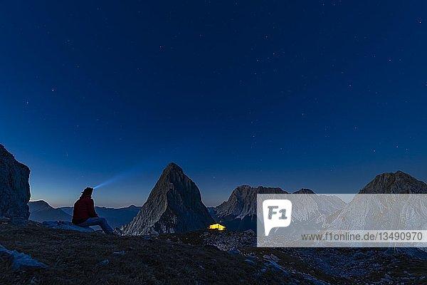 Gipfel der Sonnenspitze mit Bergsteiger und Zelt und Zugspitze im Hintergrund bei blauer Stunde  Ehrwald  Außerfern  Tirol  Österreich  Europa