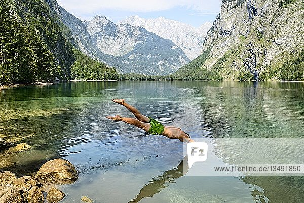 Junger Mann springt mit Kopfsprung in den Obersee  baden  Bergsee  Berglandschaft  hinten Watzmannmassiv  Salet am Königssee  Nationalpark Berchtesgaden  Berchtesgadener Land  Oberbayern  Bayern  Deutschland  Europa