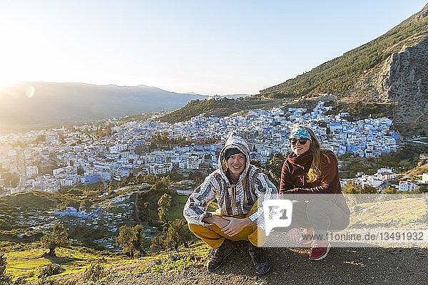 Junges Paar in marokkanischem Djellaba an Aussichtspunkt  Ausblick auf die Medina von Chefchaouen  Chaouen  Tanger-Tétouan  Marokko  Afrika