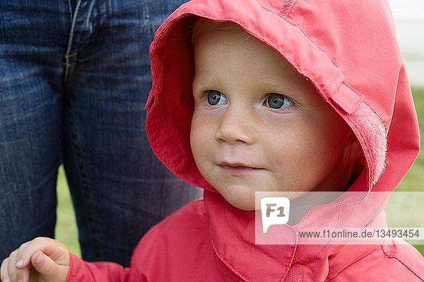 Portrait eines kleinen Mädchens mit roter Regenjacke  Mutter steht dahinter