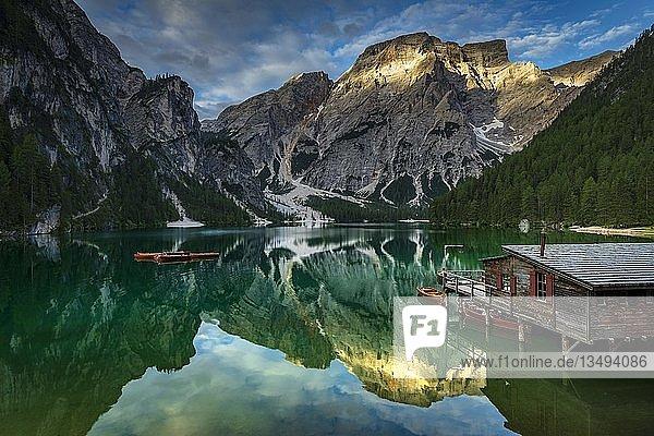 Grüner Bergsee mit Booten und Bootshaus  dahinter Seekogel Gipfel  Wasserspiegelung  Pragser Wildsee  Prags  Dolomiten  Italien  Europa