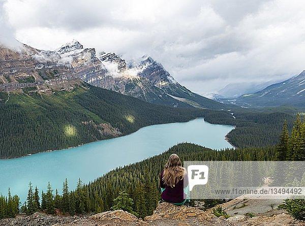 Junge Frau sitzt auf einem Stein und blickt in die Natur  türkisfarbener See  Peyto Lake  Rocky Mountains  Banff-Nationalpark  Provinz Alberta  Kanada  Nordamerika