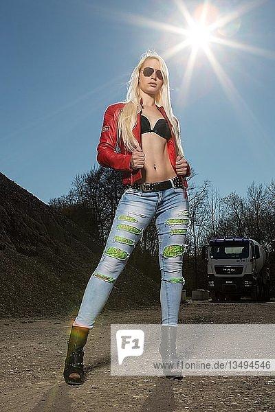 Junge Frau blond  posiert cool mit Sonnenbrille und roter Lederjacke  Fashion  Lifestyle