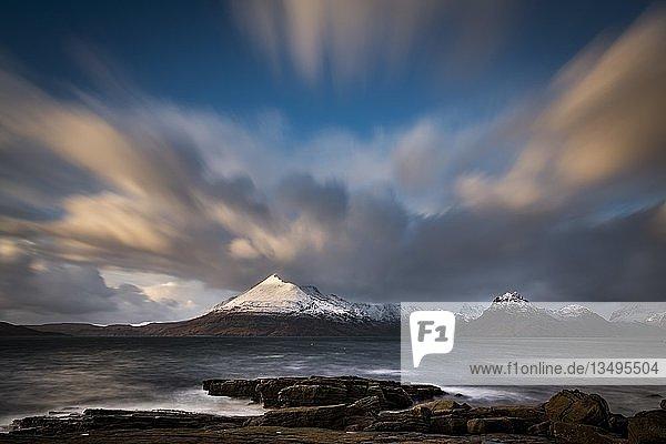 Große Felsen im Wasser der Nordsee mit verschneiten Cullin Bergen im Hintergrund  Elgol  Isle of Skye  Schottland  Großbritannien  Europa