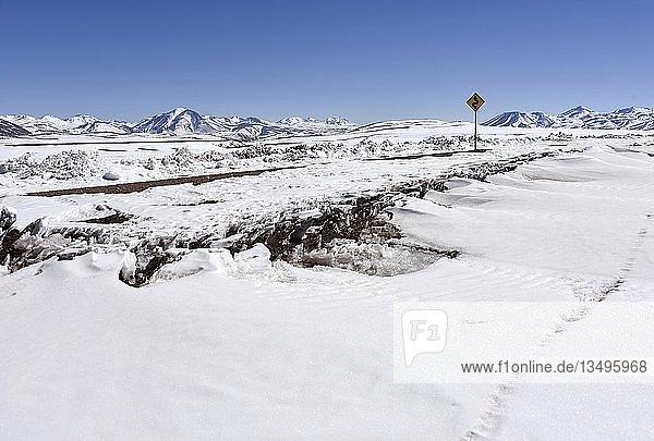 Tief verschneite Straße durch Atacama Wüste mit Verkehrsschild vor Anden  Altiplano  Bolivien  Südamerika