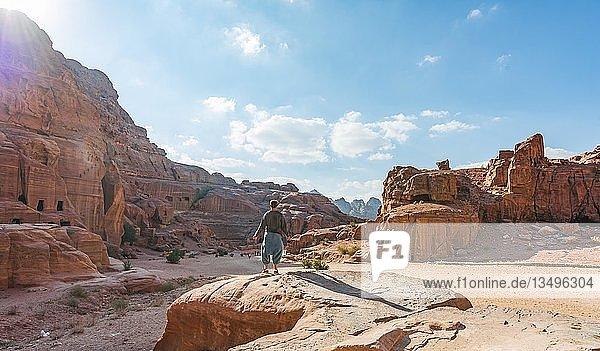 Tourist blickt auf in Felsen gehauene Häuser  Nabatäerstadt Petra  bei Wadi Musa  Jordanien  Asien