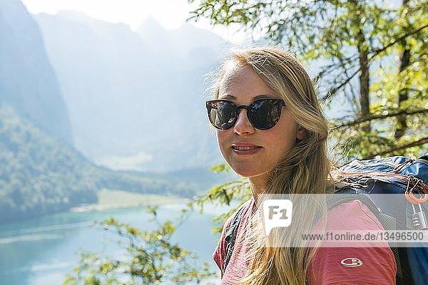 Portrait einer jungen hübschen Frau  Wanderin mit Rucksack  hinten Obersee  Nationalpark Berchtesgaden  Berchtesgadener Land Land  Oberbayern  Bayern  Deutschland  Europa