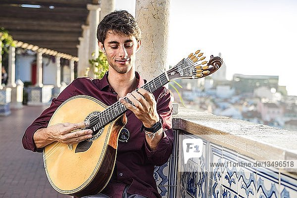Fado musician playing on unique portuguese guitar in Alfama  Lisbon  Portugal  Europe