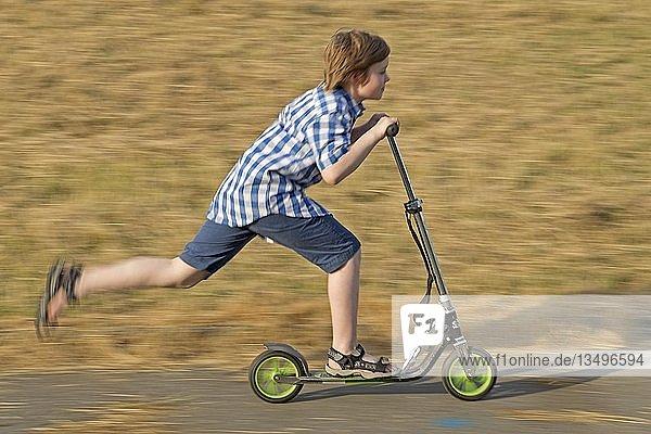 Junge fährt Roller