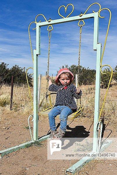 Kleines Mädchen mit rotem Hut schaukelt auf einer alten Schaukel  Patagonien  Argentinien  Südamerika