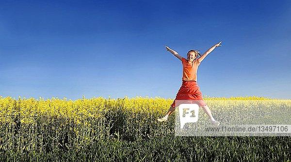 Freudig in die Höhe springendes Mädchen vor einem gelben Rapsfeld