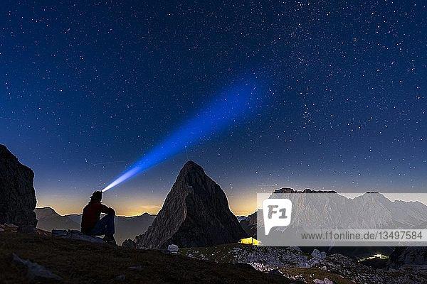 Gipfel der Sonnenspitze mit Bergsteiger und Zelt sowie Zugspitze im Hintergrund bei blauer Stunde und Sternenmimmel  Ehrwald  Außerfern  Tirol  Österreich  Europa