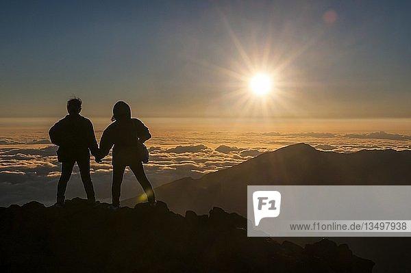 Touristen im Gegenlicht warten auf den Sonnenuntergang auf dem Gipfel des Haleakala Nationalparks  Maui  Hawaii  USA  Nordamerika