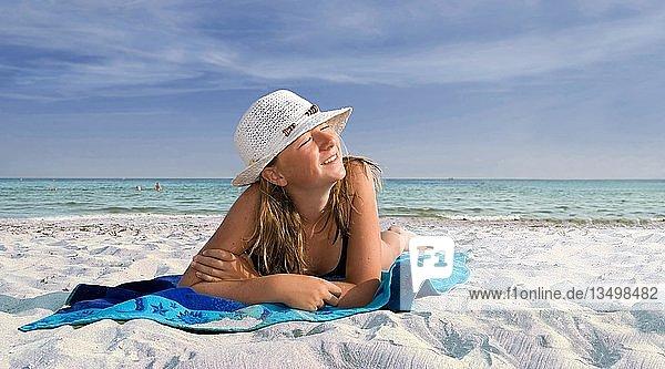Mädchen mit Sonnenhut liegend auf einem blauen Badetuch am Meer mit weißem Sandstrand
