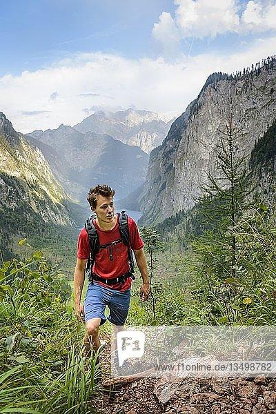 Junger Mann beim Bergsteigen  Wandern  Ausblick vom Rothsteig auf den Obersee  Königsee  Alpen  Berglandschaft  Nationalpark Berchtesgaden  Berchtesgadener Land  Oberbayern  Bayern  Deutschland  Europa