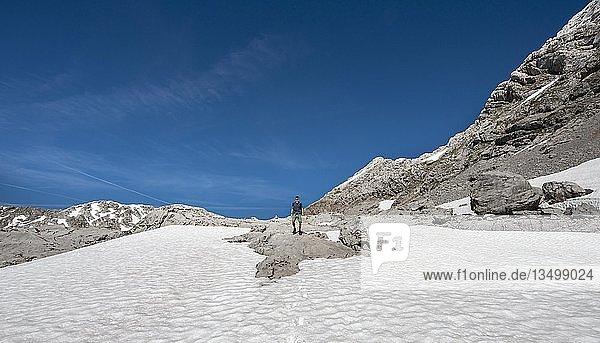 Wanderer steht auf Felsen im Schneefeld  Wanderweg zur Wasseralm über Niederbrunnsulzen  Steinernes Meer im Frühling mit Schnee  Nationalpark Berchtesgaden  Bayern  Deutschland  Europa