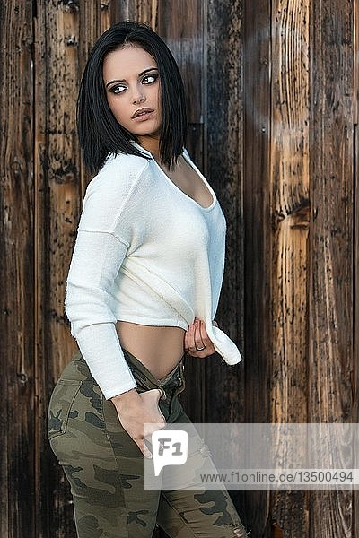 Frau mir schwarzen Haaren im weißen Pullover