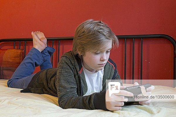 Junge mit Smartphone liegt auf seinem Bett,  Deutschland,  Europa