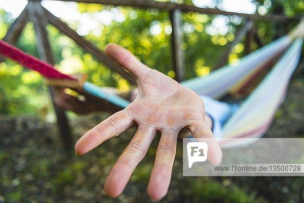 Hand streckt sich aus Hängematte  Urlaub  Italien  Europa