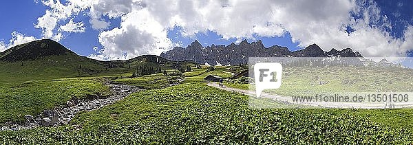 Panorama bei der Ladizalm mit Lalidererwänden  Wanderern  Wiesen und Wolkenhimmel im Karwendel  Tirol  Österreich  Europa