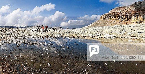 Wanderer vor einem Schmelzwassersee am Piz Boe Gipfel auf dem Sellamassiv  Sellajoch  Südtirol  Italien  Europa