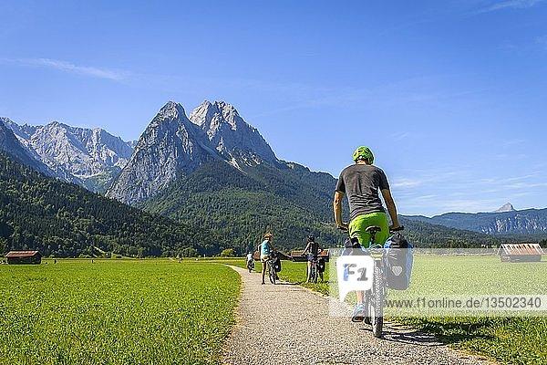 Fahrradfahrer auf Radtour fährt auf Radweg mit seinem Mountainbike  hinter Zugspitze  Tegernauweg  bei Grainau  Alpenüberquerung  Garmisch-Partenkirchen  Oberbayern  Bayern  Deutschland  Europa