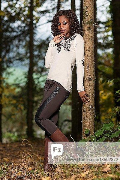 Dunkelhäutige junge Frau im herbstlichen Outfit im Wald