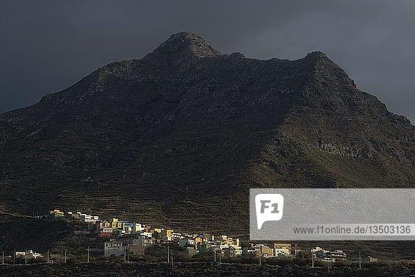 Bunte Häuser von Punta Hidalgo vor Anaga-Gebirge  dunkler Wolkenhimmel  Punta del Hidalgo  Teneriffa  Kanarische Inseln  Spanien  Europa