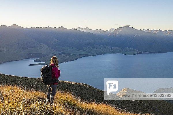 Wanderin am Isthmus Peak  Lake Wanaka und Bergpanorama bei stimmungsvollen Abendlicht  Otago  Südinsel  Neuseeland  Ozeanien