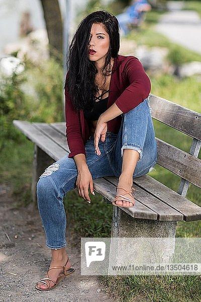 Junge Frau mit weinroter Jacke und blauen Jeans sitzt auf einer Holzbank