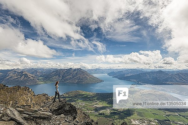 Female hiker stands on rocks in The Remarkables  overlooking Lake Wakatipu  mountains and Queenstown  Queenstown  Otago  South Island  New Zealand  Oceania