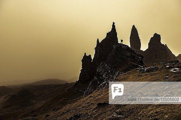 Felsen Old Man of Storr im Gegenlicht mit Fotograf auf Felsen  Portree  Isle of Sky  Schottland  Großbritannien  Europa