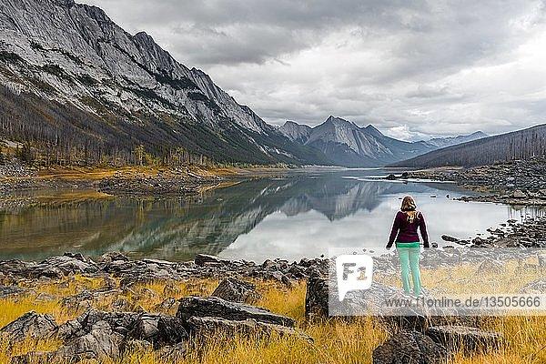 Junge Frau steht auf einem Felsen  blickt in die Landschaft  Berge spiegeln sich in einem See  Medicine Lake  Maligne Valley  Jasper National Park  Alberta  Kanada  Nordamerika