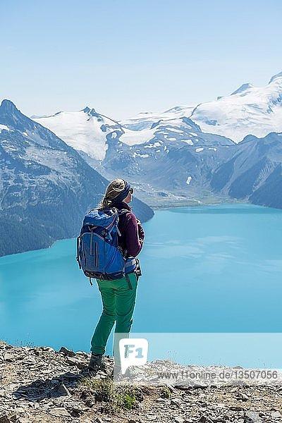 Ausblick vom Wanderweg Panorama Ridge  Wanderin auf einem Felsen  Garibaldi Lake  türkiser Gletschersee  Guard Mountain und Deception Peak  Gletscher  Garibaldi Provincial Park  British Columbia  Kanada  Nordamerika
