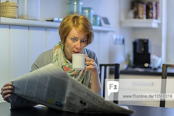 Frau sitzt am Küchentisch und liest verwundert die Zeitung  Deutschland  Europa