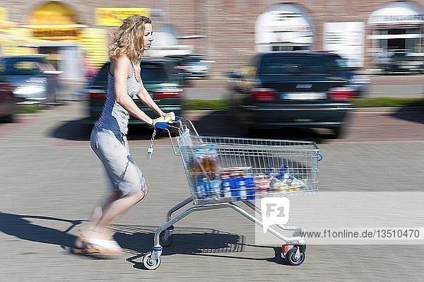 Junge Frau mit Einkaufswagen auf einem Parkplatz