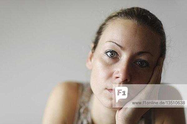 Nachdenkliche junge Frau stützt Kopf in Hand  Porträt