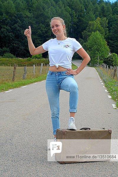 Junge Frau mit Koffer fährt per Anhalter an einer Landstraße  Scania  Schweden  Europa