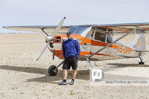 Mann lehnt an Cessna 170  Flugfeld Ganab  Namib-Naukluft-Nationalpark  Region Erongo  Namibia  Afrika