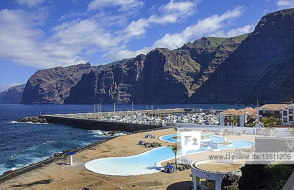 Blick von einem Hotelpool über den Hafen auf auf Los Gigantes an der Westküste  bekannt durch seine bis 450 Meter steil abfallenden Felsklippen  Teneriffa  Kanarische Inseln  Spanien  Europa