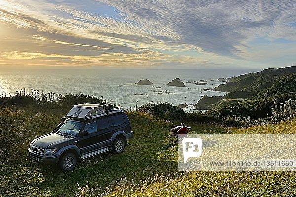 Frau sitzt bei Geländewagen an der Küste  Pazifik  Pumillahue  Insel Chiloé  Chile  Südamerika