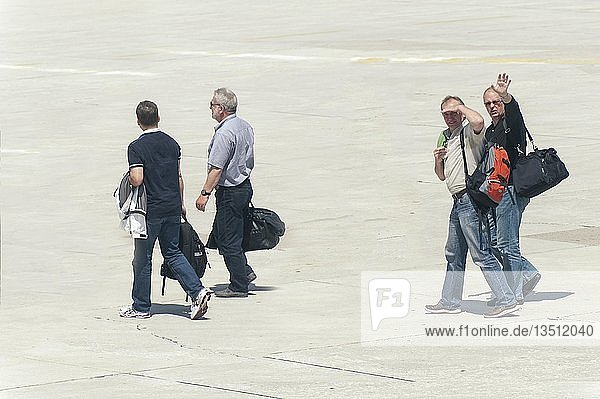 Four people walking across the tarmac to their plane  Split  Croatia  Europe