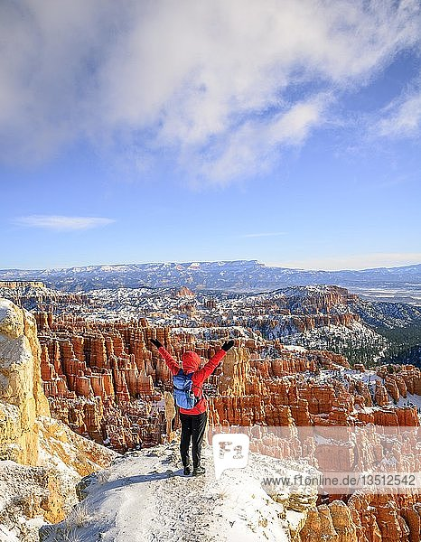 Young woman with outstretched arms overlooking the amphitheatre  bizarre snowy rocky landscape with Hoodoos in winter  Rim Trail  Bryce Canyon National Park  Utah  USA  North America